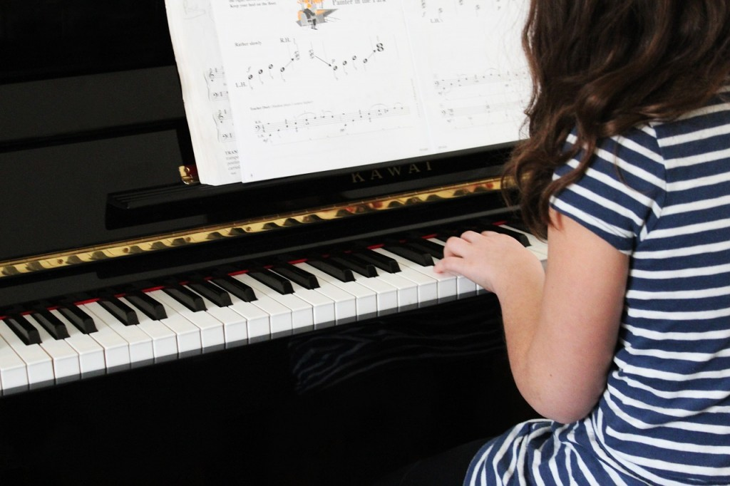 young girl practicing piano reading sheet music